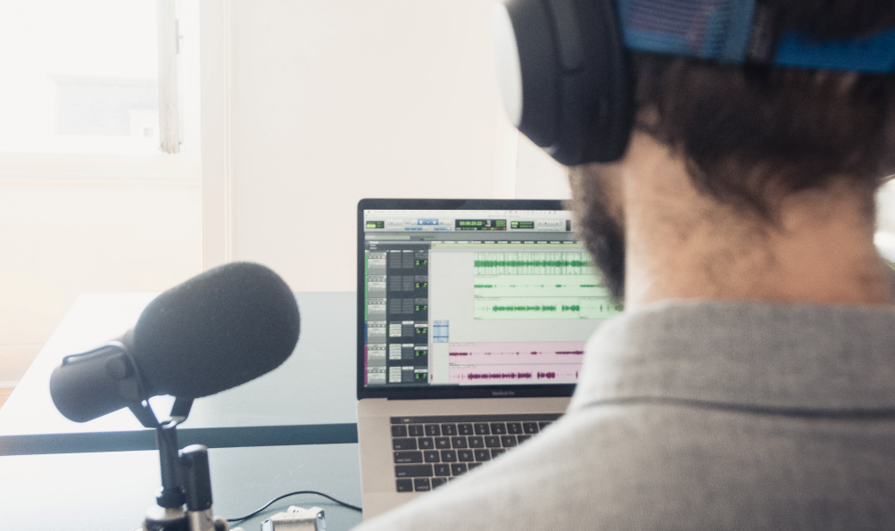 man editing podcast with microphone and laptop